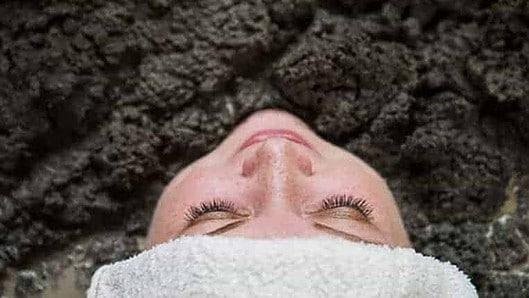 Woman soaks in mud bath